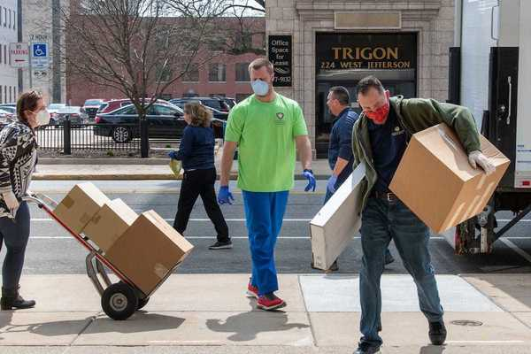 Workers from St. Joesph County Department of Health unload boxes of donated protective gear from Notre Dame at the County City Building in South Bend.