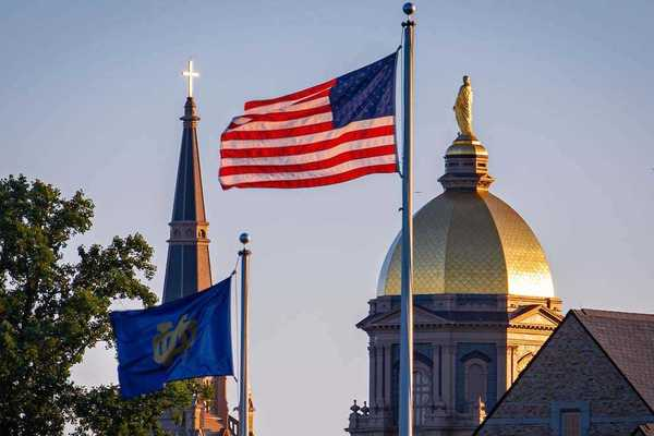 The Notre Dame and U.S. flags fly in front of the campus skyline.